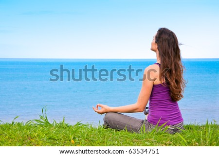 A beautiful young woman sitting meditating with a view of a lovely blue ocean - stock photo
