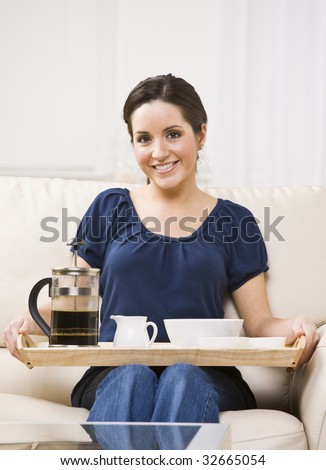 A beautiful young woman sitting on a couch and holding a breakfast tray.  She is smiling at the camera.  Vertically framed shot.