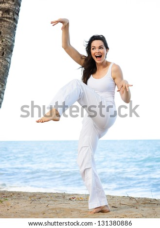 A beautiful young woman smiling as she is doing a silly and funny yoga pose on a beach.