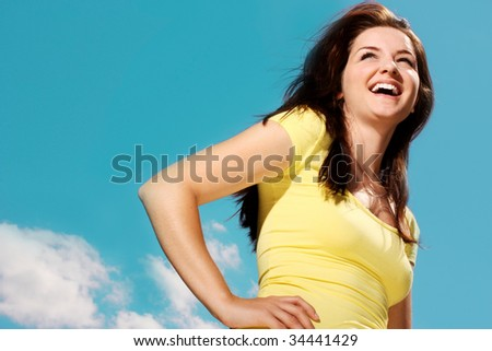 A beautiful young woman smiling in front of a sunny blue sky.