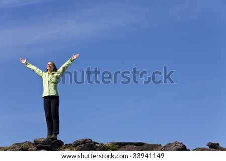 A beautiful young woman stands on the horizon arms raised celebrating reaching the top of a mountain.