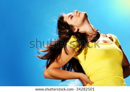 A beautiful young woman throwing her head back in the sun outdoors in front of a blue sky.