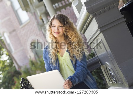 A beautiful young woman using a laptop outdoors
