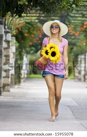 A beautiful young woman walking through a flower covered walkway carrying a basket of sunflowers