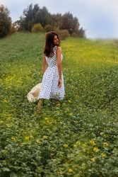 a beautiful young woman walks through a field in a white dress with peas, holding a straw hat with one hand, and touching flowers with the other