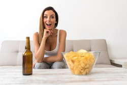 A beautiful young woman watching thrilled something on a Screen with Beer and potato Chips.