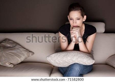 A beautiful young woman watching TV at home alone.