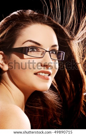 A beautiful young woman wearing fashionable glasses with her hair in motion.