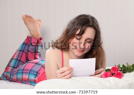 A beautiful young woman wearing pink pajamas, lying in bed reading a letter with three roses on the pillow.