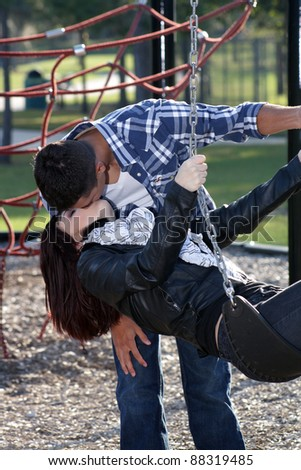 A beautiful young woman with auburn hair leans backward in a swing to kiss her handsome mate.