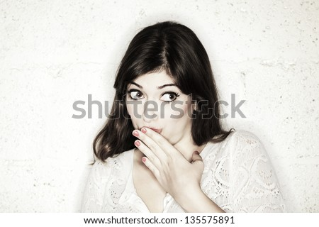 A beautiful young woman with her eyes wide open glancing sideways, with her hand covering her mouth.Looks like she is feeling shy towards something, or maybe guilty. Either way, she is very cute.