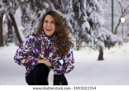 A beautiful young woman with long hair in a winter snowy park is not posing but laughing frankly happily .. Winter portrait of a woman with brown hair among the snow.