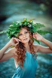 a beautiful young woman with red hair and a wreath of flowers and fern in the forest celebrates Solstice Day, mid-summer.