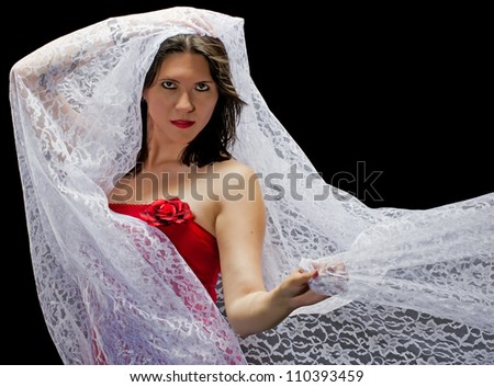 A beautiful young woman with white lace blowing around her face and shoulders isolated on a black background.