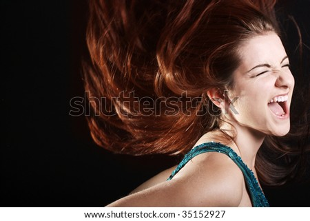 A beautiful young woman wither her fiery hair in motion screaming.