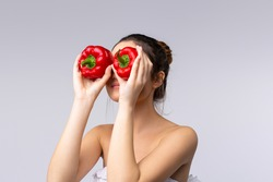 A beautifull brunette, wrapped in a towel, holds 2 bell peppers next to her eyes, promoting the concept of health, rational and balanced nutrition. Health is the slogan of life.