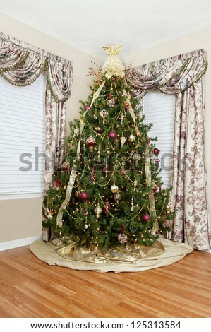 A beautifully decorated indoor Christmas tree with angel on top, vertical with copy space
