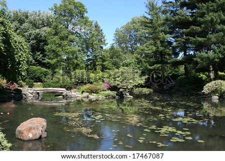 A beautifully landscaped koi pond with bridge