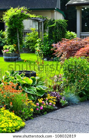 A beautifully manicured yard with a garden full of annuals and perennials.