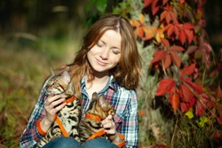 A beautifulwoman sits in the autumn forest with a Bengal cat in her arms.