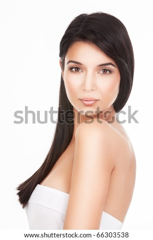 a beauty portrait of a young woman, shot on white background. she looks over her shoulder, straight to the camera.