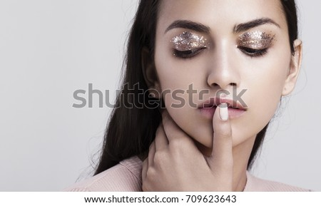 Stock Photo A beauty portrait of an indian model with glitter makeup touching her lips.