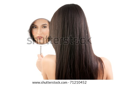 a beauty studio picture of a young woman looking in a mirror, while her back is turned to the camera. the mirror held over her left shoulder reflects her face.