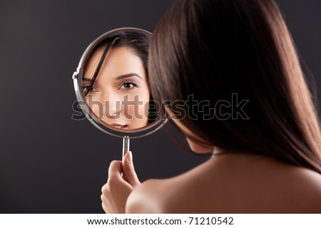 a beauty studio picture of a young woman looking in a mirror, while her back is turned to the camera. the mirror held over her left shoulder reflects her smiling face.
