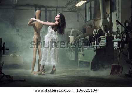 A beauty woman dances with a wooden dummy
