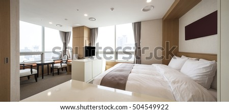 A bed room with bed, brown blanket(covers, comforter, curtain, bedding, bedclothes, quilt), lighting, television(tv, led, lcd), chair, table at the hotel, seoul, south korea. #504549922