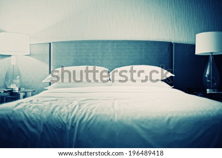 A bed with white sheets and white pillows.