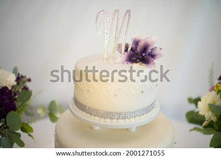 A Bedazzled M Sits On Top of a Wedding Cake Photo stock ©