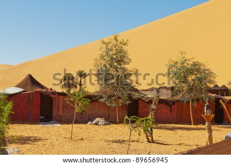 A bedouin camp against one of the huge orange sand dunes in Erg Chebbi, Morocco