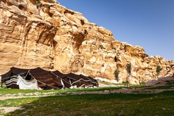 A bedouin tent made of goat hair set up in the desert landscape of Jordan, near Petra. Image features the rock formations and shepherd dogs by this nomadic tent.