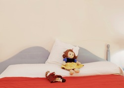 A bedroom with two rag dolls on the bed, a red blanket and a warm lighting. Home, kids, childhood.