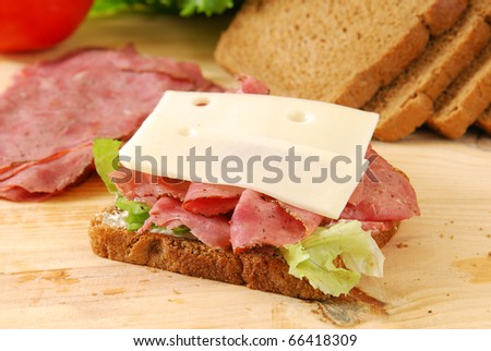 A beef and cheese sandwich being prepared on a cutting board