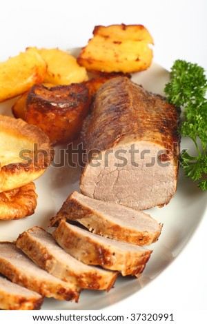 """A beef """"eye roast"""" joint, sliced into medallions, on a plate with roast potatoes and Yorkshire puddings. - stock photo"""
