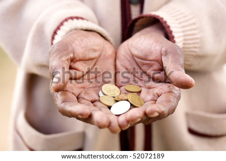 A beggar holding out his hands filled with coins.