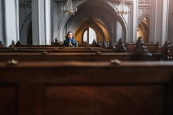 A believing woman sits on a bench in the church and prays to God with hands clasped