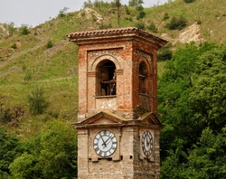 A bell tower with a clock, in baroque style, with a hill in the background in Piedmont, Italy. Concept of ancient constructions