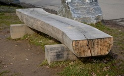 A bench in a park made of one half of a massive trunk. It is a heavy wooden product with a natural, durable appearance. Large stones around define the area for pedestrians