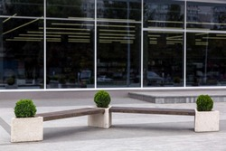 A bench near the facade with panoramic windows of the shopping center, a wooden bench with stone flowerpots for the bushes.