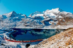 A Bernina Express train traveling along the lake shore of Lago Bianco & alpine mountains towering under blue sky in background after a snowfall in autumn, near Ospizio Bernina, in Grisons, Switzerland