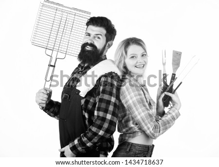 A better grill for a better cook. Happy hipster and sexi girl holding picnic set for barbecue. Family couple having picnic party. Sexy woman and bearded man enjoying picnic or cookout. Family picnic. #1434718637