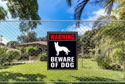 A Beware of Dog Sign on a fence near a bungalow house. Warning to visitors or burglars. Security and protection in a residential home concept.