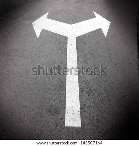 A bi-directional arrow symbol on asphalt road for the concept of choice at a junction.