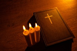 A Bible and three burning candles on a wooden table. Christian sermon. Christian faith. Protestantism, Catholicism and Orthodoxy. Faith in Jesus Christ. Study of the word of God.