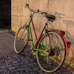 A bicycle leaned against a wall on an alleyway