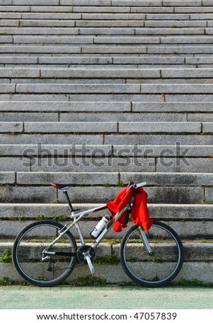 A bicycle leaning against the stone stairs, with a red clothes on it.