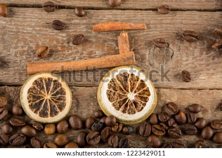 A bicycle made from pieces of dried lemons and cinnamon sticks, a path made from coffee beans against rough wooden boards, flatly #1223429011
